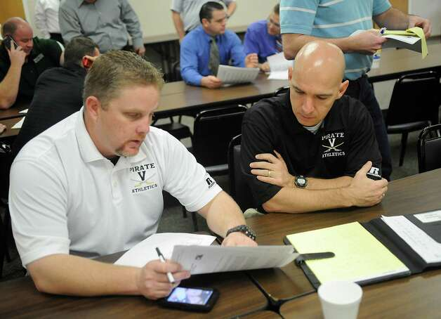Vidor coaches Richard Robinson, left, and Dwaine Dubois, right, look over their schedules and the realignment paperwork. The high school sports realignment from the UIL was released at 9:00 am Thursday morning. Coaches from the area gathered at the Region 5 education service center in Beaumont for the release of the districts and to plan scheduling of games for next season.  Dave Ryan/The Enterprise Photo: Dave Ryan