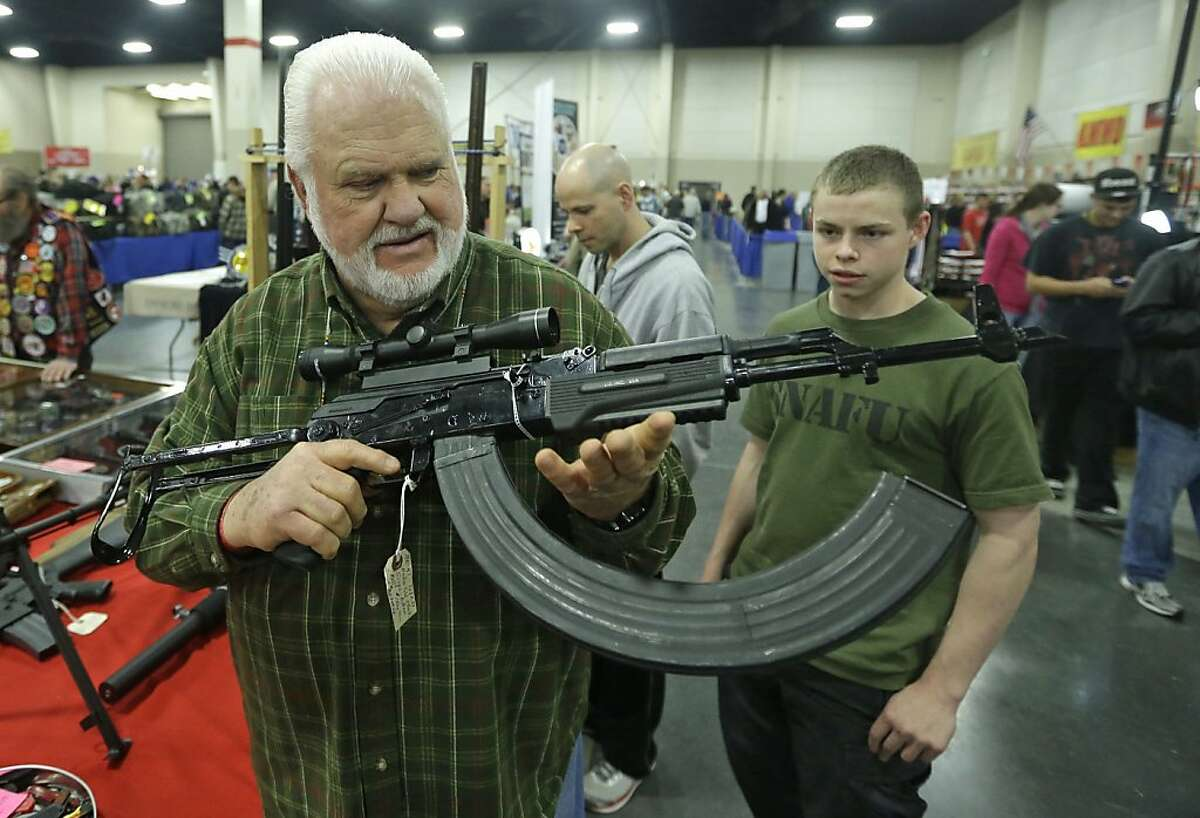 Retired policeman Ken Halterman, holds a AK-47 with a 75 round clip during the Rocky Mountain Gun Show Sunday, March 3, 2013, in Sandy, Utah. (AP Photo/Rick Bowmer)