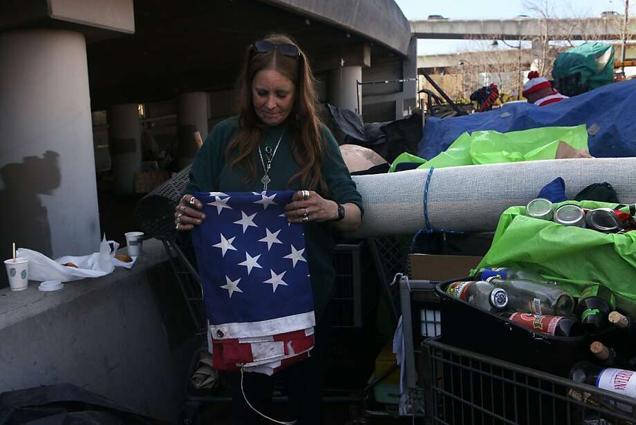 Lisa Ross folds a flag given to her and her boyfriend beneath the Interstate 280 on-ramp in San Francisco, Calif., as she packs belongings on Monday, March 11, 2013. Photo: Liz Hafalia, The Chronicle