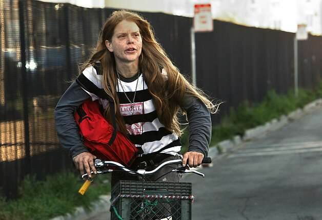 Jensina Hardig, 35 years old, rides through the homeless encampment beneath the Interstate 280 on-ramp in San Francisco, Calif., after leaving earlier this morning on Monday, March 11, 2013.   The encampment was forced to leave this morning with a permanent fence planned to keep the camp out of the area. Photo: Liz Hafalia, The Chronicle
