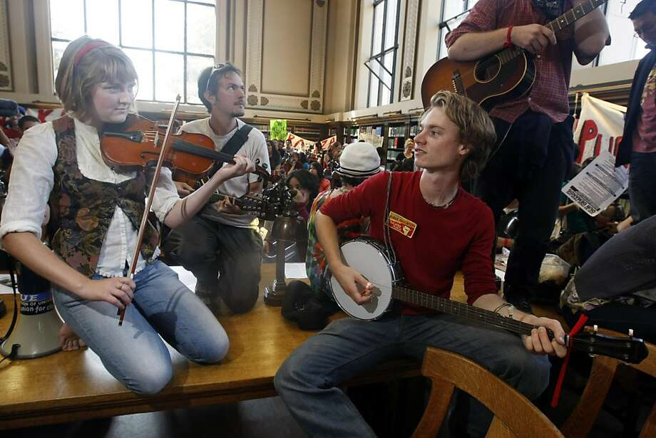 Lesley Haddock (left), Andrew Snyder, and Gabe Schwartzman perform at a 2010 protest in UC Berkeley's Doe library. Students protested fees and other issues at UCs around the state. Photo: Adm Golub, The Chronicle
