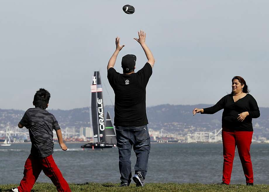 The Macedo family, Isaac (left), Benny and Annie played some touch football in the small park next to McCovey Cove near AT&T park while an Oracle racing vessel practiced in the bay. No rain and a week of spring fever is prompting many in San Francisco, Calif. to spend their lunch hours outside Monday March 11, 2013. Photo: Brant Ward, The Chronicle