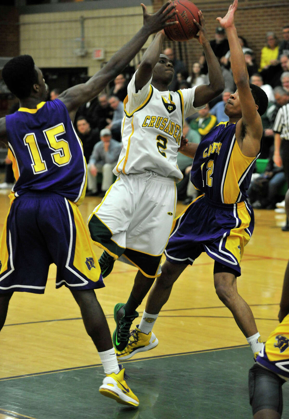 Trinity Catholic's Schadrac Casimir shoots while under pressure from Career Magnet's Matt Hamiliton, left, and Lyman Depriest during their Class L state quarterfinal game at Trinity Catholic High School in Stamford on Monday, March 11, 2013. Trinity Catholic won, 58-45.
