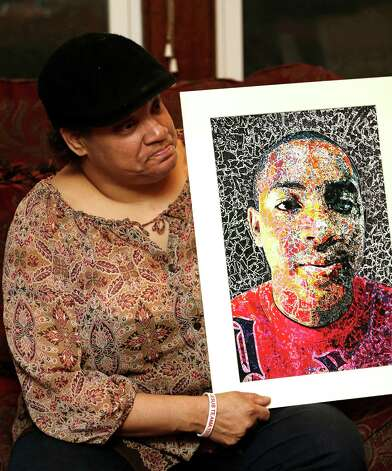 Lisa Williamson holds up a self-portrait of her son Brandon Murray, Monday, March 11, 2013, in Warren, Ohio. Investigators spent Monday trying to piece together why eight teenagers were crammed into a speeding SUV without the owner's permission when it flipped over into a pond, killing six of them, including Murray. (AP Photo/Tony Dejak) Photo: Tony Dejak