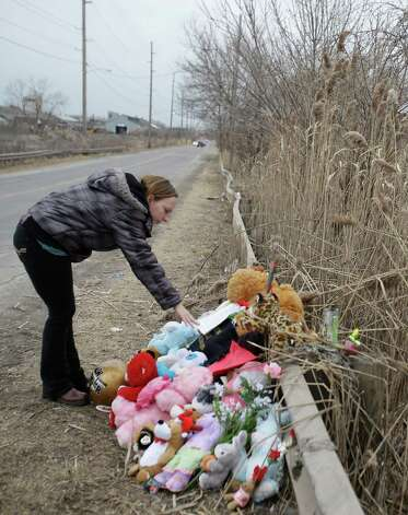 Shannon Whetstone reads notes left at the scene where six teens died early Sunday in Warren, Ohio, on Monday, March 11, 2013. Two teens who escaped a crash that killed six friends in a swampy pond wriggled out of the wreckage by smashing a rear window and swimming away from the SUV, a state trooper said Monday. (AP Photo/Tony Dejak) Photo: Tony Dejak