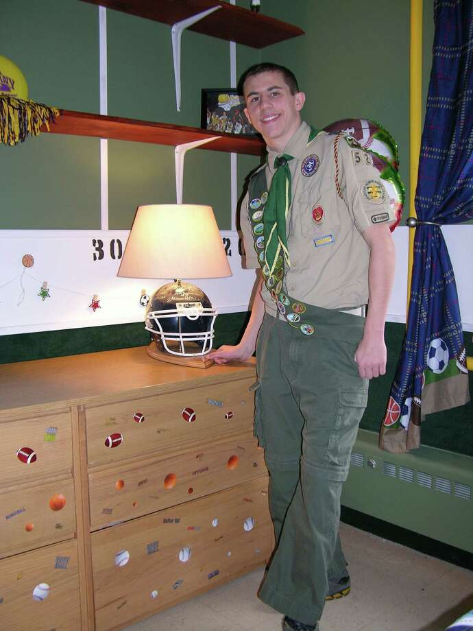 Berlin Central High School freshman Stephen Pelletier shows off a lamp made out of an old football helmet and signed by his Pop Warner teammates in a room he renovated for his Eagle Scout project at St. Catherine's Center for Children in Albany. (Brian Bell)