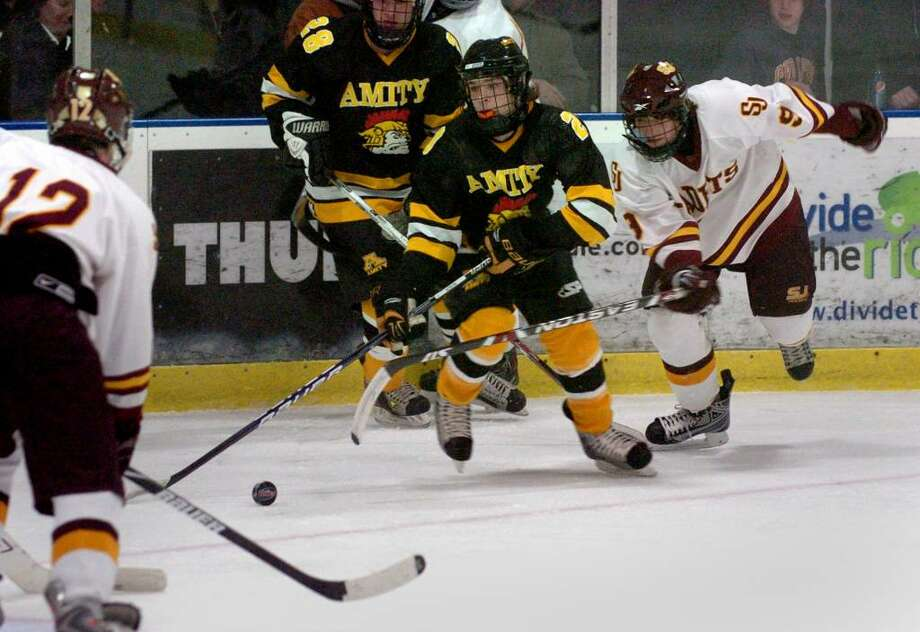 Amity's #20 Luke Sacramore, center, tries to move the puck while between St. Joseph's #12 Curtis McKeon, left, and #9 Christian Keator, during hockey action at The Rinks in Shelton on Saturday Jan. 02, 2010. Photo: Christian Abraham / Connecticut Post