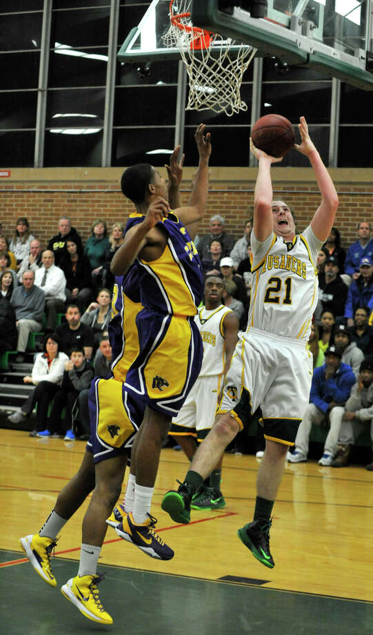 Trinity Catholic's Dan O'Leary snares a rebound and puts up a shot during their Class L state quarterfinal game against Career Magnet at Trinity Catholic High School in Stamford on Monday, March 11, 2013. Trinity Catholic won, 58-45. Photo: Jason Rearick / The Advocate
