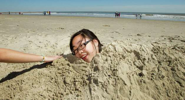 Mai Tran, 13, laughs as she is buried in the sand by her cousin, AnhTa, while enjoying their spring break on the beach near 53rd and Seawall Monday, March 11, 2013, in Galveston. Photo: Brett Coomer, Houston Chronicle / © 2013 Houston Chronicle