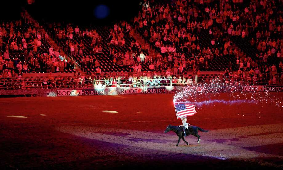 3/11/13:  A girls carries the American flag as light peeks though the windows on the floor in the Houston BP Super Series V Round 2 Houston Rodeo at  Reliant Stadium in Houston, Texas. Photo: Thomas B. Shea, For The Chronicle / © 2013 Thomas B. Shea