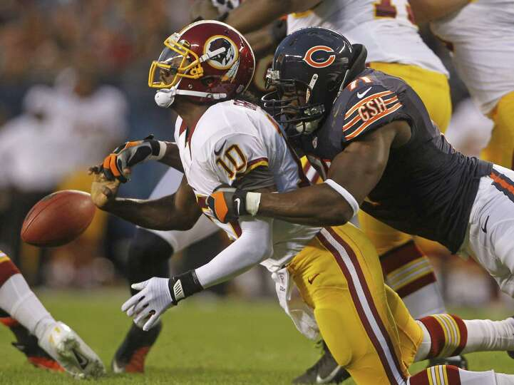 Bears defensive end Israel Idonije (right) brings down Redskins QB Robert Griffin III for one of the