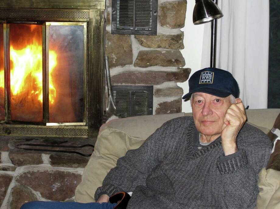 In this March 2012 family photo provided by Remi Joyeuse, Rene Joyeuse sits next to a fireplace. Joyeuse, a retired physician, was 92 when he died last June after battling Alzheimer's disease for more than a decade. His family was crushed to learn that the WWII vet, who shot his way out of a Nazi ambush and provided vital information to the Allies ahead of the D-Day invasion, wasn't eligible for burial at Arlington National Cemetery. (AP Photo/Remi Joyeuse)