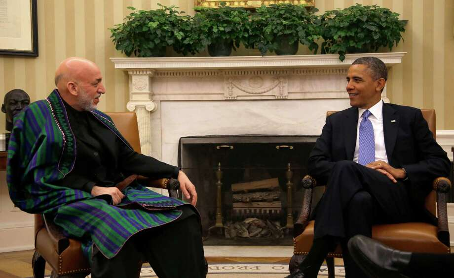 FILE - In this Jan. 11, 2013 file photo, President Barack Obama meets with Afghan President Hamid Karzai in the Oval Office of the White in Washington. The troubled U.S. alliance with Afghan President Hamid Karzai hits a new low with his startling accusation that the U.S. is colluding with the Taliban to keep Afghanistan weak. But with President Barack Obama committed to two more years of combat, Karzai appears to be able to have it both ways – to gain political favor at home with anti-American rhetoric and to gain military protection from abroad against the Taliban. (AP Photo/Pablo Martinez Monsivais, File) Photo: Pablo Martinez Monsivais