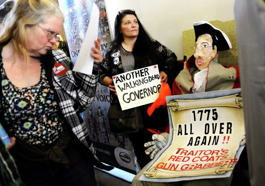 "Claudette Bleidner, center, of Southbury, Conn., stands next to a caricature  she made of Gov. Dannel P. Malloy dressed as a Redcoat soldier,  as a woman reads information of upcoming gun legislation during a ""lobby day"" held by the National Rifle Association and and other gun rights groups at the Legislative Office Building in Hartford, Conn., Monday, March 11, 2013. Both sides of the gun control issue are increasing pressure on Connecticut lawmakers, who are close to voting on changes to state law stemming from the deadly shooting at Sandy Hook Elementary School in Newtown. (AP Photo/Jessica Hill) Photo: Jessica Hill"