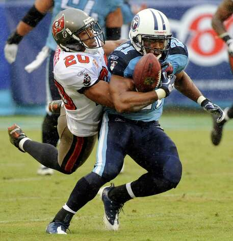 FILE - In this Sunday, Nov. 27, 2011 file photo, Tampa Bay Buccaneers cornerback Ronde Barber (20) knocks the ball out of the grasp of Tennessee Titans running back Javon Ringer (21) in the second quarter of an NFL football game in Nashville, Tenn. Most of the big names hitting NFL free agency in 2013 aren't big stars anymore. While Ed Reed is coming off a Super Bowl season in Baltimore and Wes Welker catches 100 passes every year, this crop is more about aging defensive players such as Charles Woodson, Brian Urlacher and Barber. (AP Photo/Frederick Breedon, File) Photo: Frederick Breedon