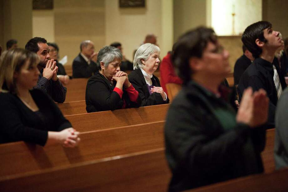 Church members pray at a Mass at Houston's Co-Cathedral of the Sacred Heart on Monday. The conclave to elect a new pope starts on Tuesday at the Sistine Chapel. Photo: Eric Kayne, For The Chronicle / © 2013 Eric Kayne