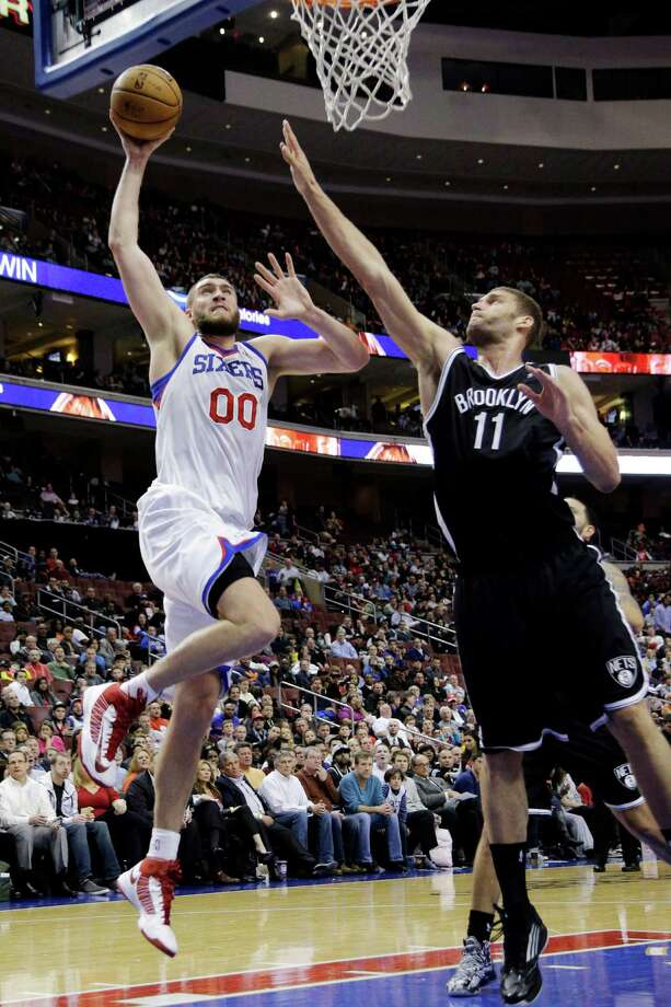 Philadelphia 76ers' Spencer Hawes (00) shoots as Brooklyn Nets' Brook Lopez defends during the second half of an NBA basketball game, Monday, March 11, 2013, in Philadelphia. Philadelphia won 106-97. (AP Photo/Matt Slocum) Photo: Matt Slocum