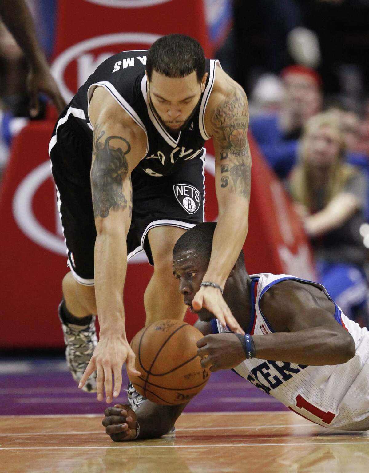 Jrue Holliday (bottom) and Deron Williams fight for the ball in Philadelphia's 106-97 victory.