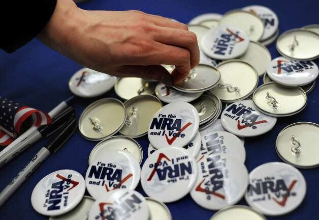 "A woman grabs a button during a ""lobby day"" held by the National Rifle Association and other gun rights groups at the Legislative Office Building in Hartford, Conn., Monday, March 11, 2013. Both sides of the gun control issue are increasing pressure on Connecticut lawmakers who are close to voting on changes to state law stemming from the deadly shooting at Sandy Hook Elementary School in Newtown. Photo: Jessica Hill, Associated Press/Jessica Hill / Associated Press"