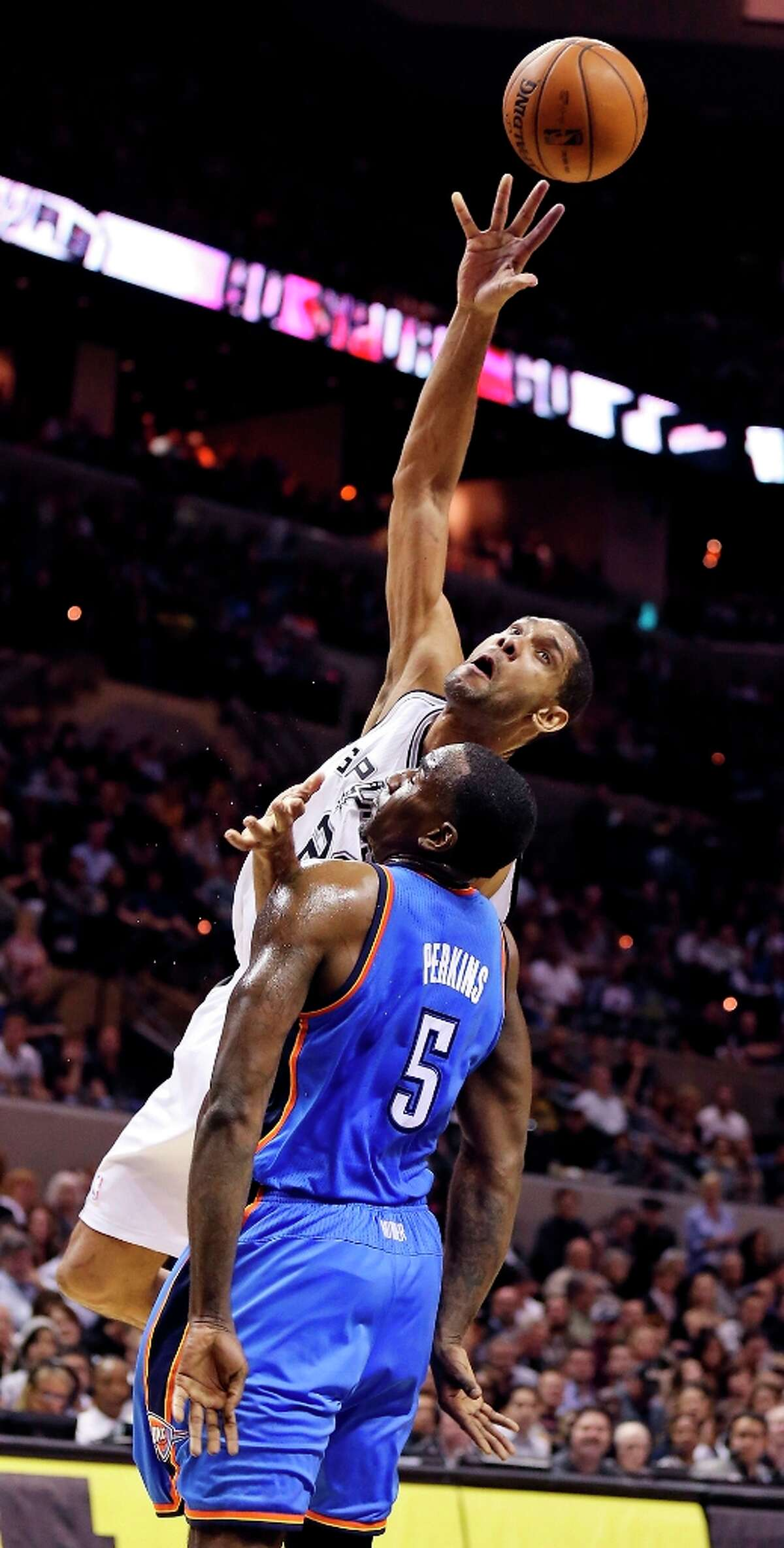 The Spurs' Tim Duncan shoots over Oklahoma City Thunder's Kendrick Perkins during first half action Monday, March 11, 2013 at the AT&T Center.