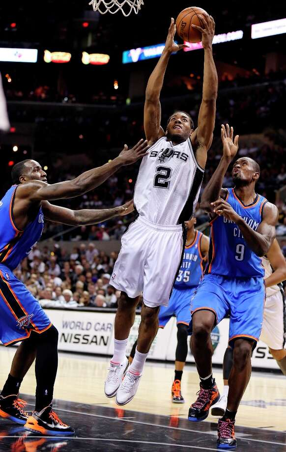 The Spurs' Kawhi Leonard drives to the basket between Oklahoma City Thunder's Kendrick Perkins and Serge Ibaka during second half action Monday, March 11, 2013 at the AT&T Center. The Spurs won 105-93. Photo: Edward A. Ornelas, San Antonio Express-News / © 2013 San Antonio Express-News