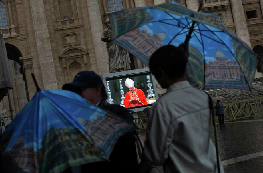 Faithful protect themselves from the rain as they follow a mass inside St. Peter's Basilica celebrated by Cardinal Angelo Sodano, seen on a giant screen in St. Peter's Square, Tuesday, March 12, 2013. Cardinals enter the Sistine Chapel on Tuesday to elect the next pope amid more upheaval and uncertainty than the Catholic Church has seen in decades: There's no front-runner, no indication how long voting will last and no sense that a single man has what it takes to fix the many problems. Photo: Emilio Morenatti