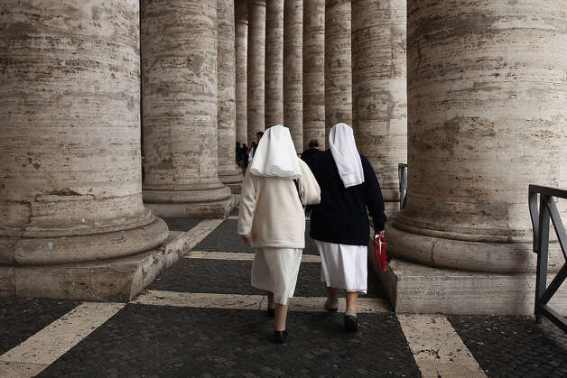 Nuns walk under the colonnade as a rain storm passes over St Peter's Square on March 12, 2013 in Vatican City, Vatican. Pope Benedict XVI?s successor is being chosen by the College of Cardinals in Conclave in the Sistine Chapel. The 115 cardinal-electors, meeting in strict secrecy, will need to reach a two-thirds-plus-one vote majority to elect the 266th Pontiff. Photo: Dan Kitwood, Getty Images / 2013 Getty Images