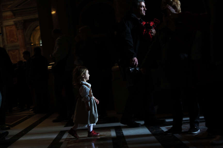 A child stands near the entrance of St Peter's Basilica during the Pro Eligendo Romano Pontifice Mass at St Peter's Basilica, after which Cardinals will enter the conclave to decide who the next pope will be on March 12, 2013 in Vatican City, Vatican. Cardinals are set to enter the conclave to elect a successor to Pope Benedict XVI after he became the first pope in 600 years to resign from the role. The conclave is scheduled to start on March 12 inside the Sistine Chapel and will be attended by 115 cardinals as they vote to select the 266th Pope of the Catholic Church. Photo: Spencer Platt, Getty Images / 2013 Getty Images