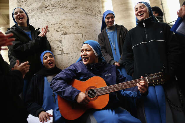 Nuns from the 'Instituto Serve del Signore, E Della Vergine Di Matara' sing hymns under the colonnade in St Peter's Square on March 12, 2013 in Vatican City, Vatican. Pope Benedict XVI?s successor is being chosen by the College of Cardinals in Conclave in the Sistine Chapel. The 115 cardinal-electors, meeting in strict secrecy, will need to reach a two-thirds-plus-one vote majority to elect the 266th Pontiff. Photo: Dan Kitwood, Getty Images / 2013 Getty Images