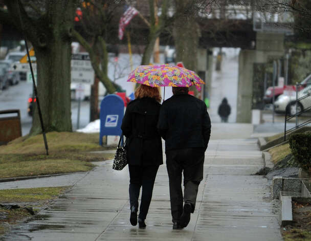 A woman and man share a small umbrella in an attempt to keep off the rain on River Street in downtown Milford, Conn. on Tuesday, March 12, 2013. Photo: Brian A. Pounds / Connecticut Post