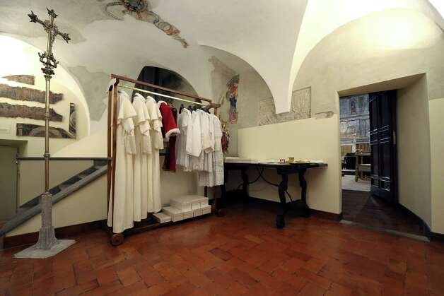 "This handout picture released by the Press office shows the ""Room of Tears"", a small room next to the Sistine Chapel (back-R), with the vestments of the next Pope displayed in three different sizes, before the start of the conclave at the Vatican on March 12, 2013. Cardinals moved into the Vatican today as the suspense mounted ahead of a secret papal election with no clear frontrunner to steer the Catholic world through troubled waters after Benedict XVI's historic resignation. The 115 cardinal electors who pick the next leader of 1.2 billion Catholics in a conclave in the Sistine Chapel will live inside the Vatican walls completely cut off from the outside world until they have made their choice. AFP PHOTO/OSSERVATORE ROMANO