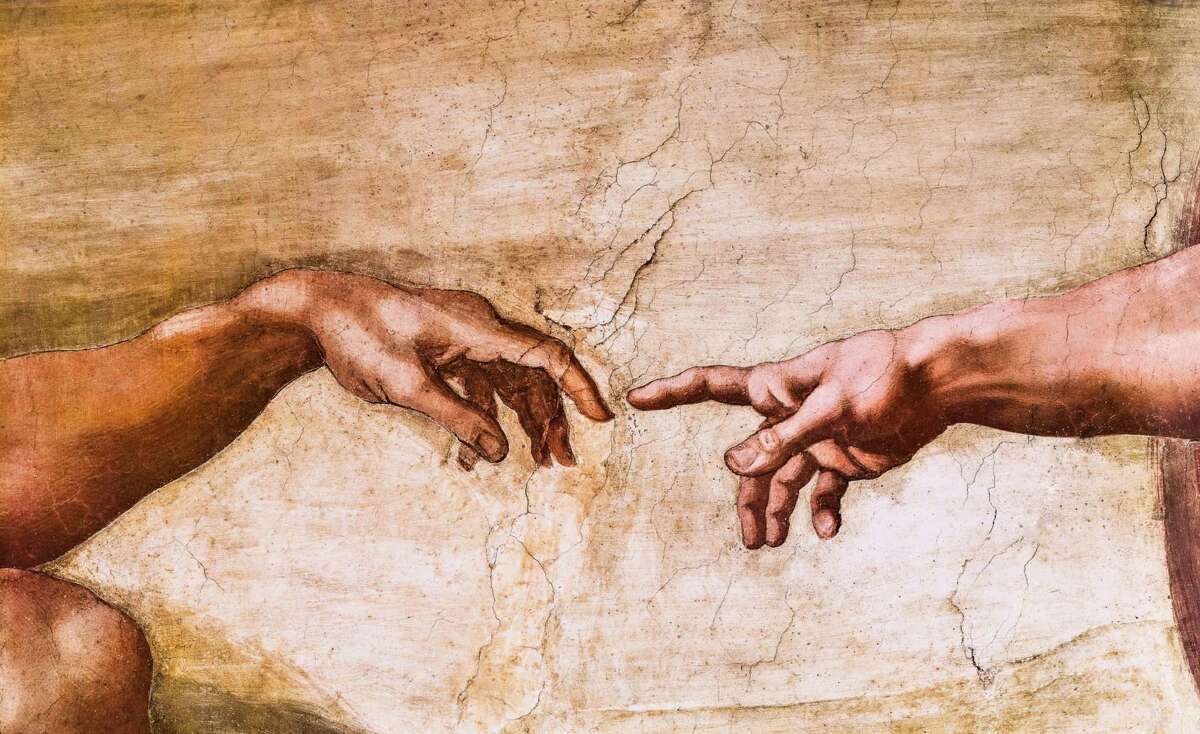 Close-up of God and Adam's hands in the Sistine Chapel.
