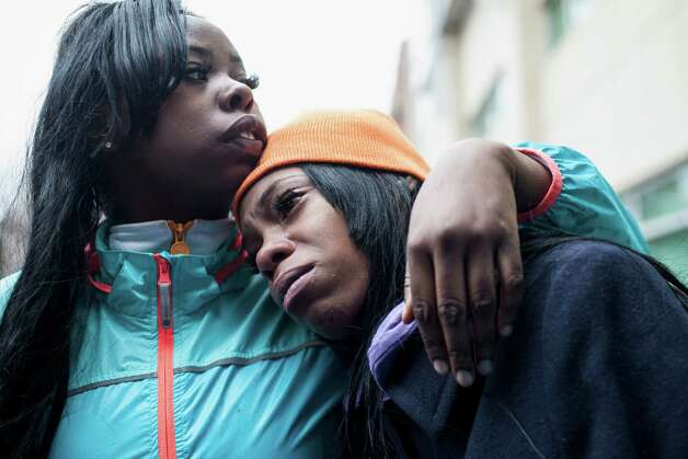 In this Monday, March 11, 2013 photo, April Jackson, left, comforts Dominique Young, the aunt of 6-month-old Jonylah Watkins, outside Comer Children's Hospital in Chicago, after the baby was shot five times while her father was changing her diaper in a parked minivan in Chicago's Woodlawn neighborhood. The Cook County Medical Examiner's office announced Tuesday morning that the baby died from her wounds. Her father, Jonathan Watkins, remains in critical condition at Northwestern Memorial Hospital.   CHICAGO LOCALS OUT, MAGS OUT Photo: Chicago Sun-Times, Jessica Koscielniak