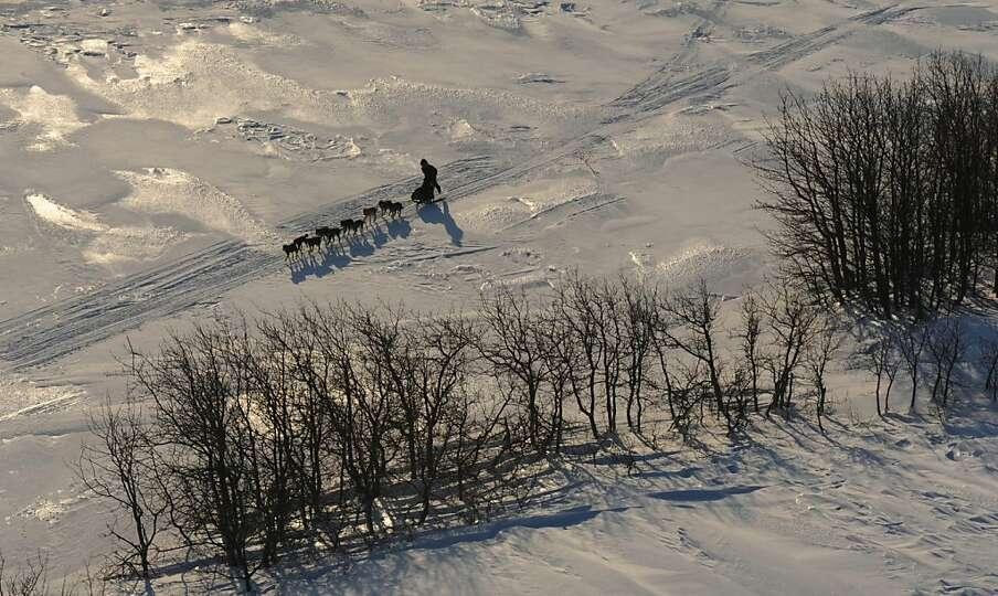A musher kicks while traveling to Koyuk in Alaska during the Iditarod Trail Sled Dog Race on Monday,
