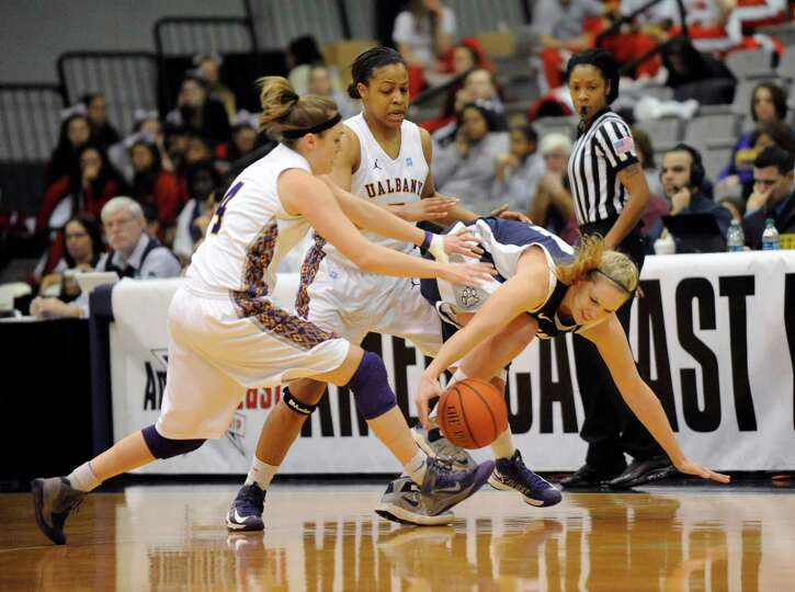 UAlbany's Sarah Royals ,left, and teammate Ebony Henry ,center, defend against UNH's Jilliane Friel