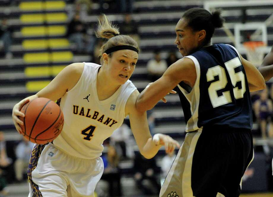 UAlbany's Sarah Royals (4) is defended by UNH's Lauren Wells ( 25) during the semifinal game of the America East tournament in Albany, N.Y., Sunday, March 10, 2013. UAlbany won 71-57. (Hans Pennink / Special to the Times Union) College Sports Photo: Hans Pennink, Times Union / Hans Pennink