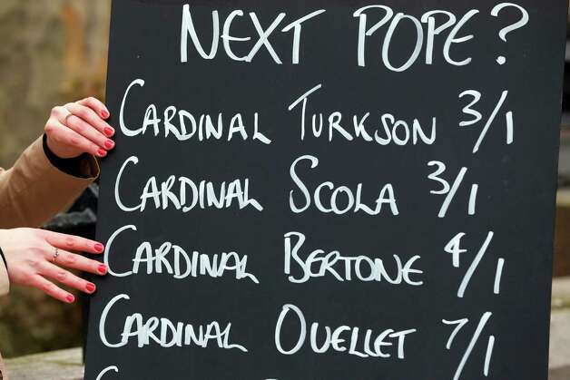 FILE - In this March 1, 2013 file photo, Jessica Bridge, a spokesperson with a betting company, poses for members of the media, next to a board with odds regarding the possible new Pope, central London. Bookmakers in betting-mad Britain are cashing in on the Roman Catholic conclave to select a new pope as cardinals began their deliberations at the Vatican on Tuesday, March 12, 2013. Photo: Lefteris Pitarakis