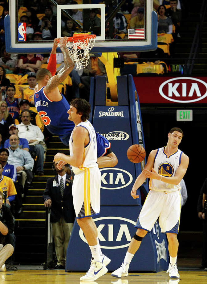 New York Knicks center Tyson Chandler dunks over Golden State Warriors center Andrew Bogut (center) and guard Klay Thompson during the first half. Photo: Beck Diefenbach, Special To The Chronicle / ONLINE_YES