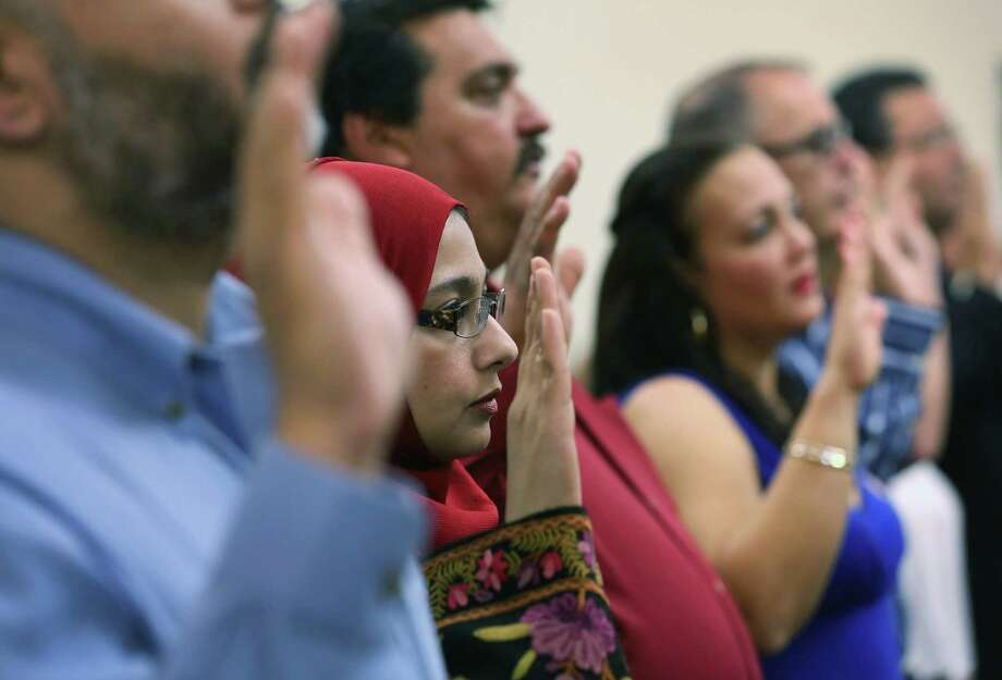 Not allowing illegal immigrants the chance to someday raise their hands in a citizenship ceremony such as this one in Florida is to injure the notion of a fair America. Photo: John Moore, Getty Images / 2013 Getty Images