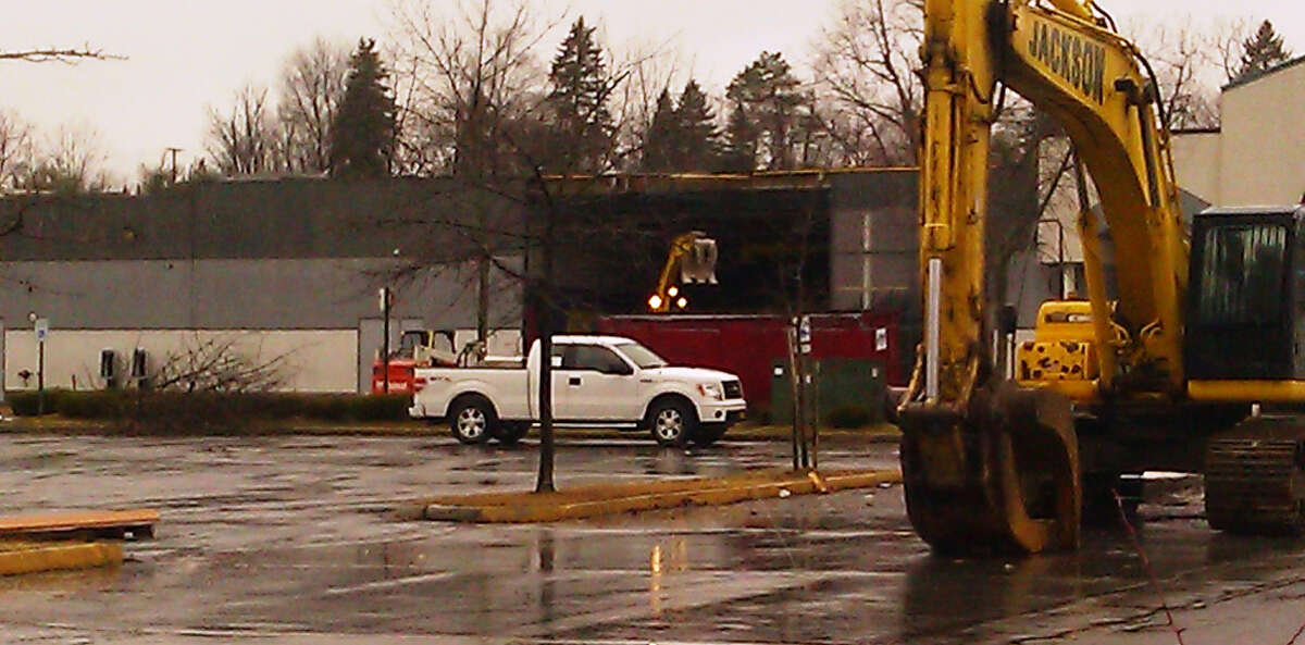 An excavating machine loads debris into a dumpster Tuesday afternoon as demolition at Latham Circle Mall gets under way.