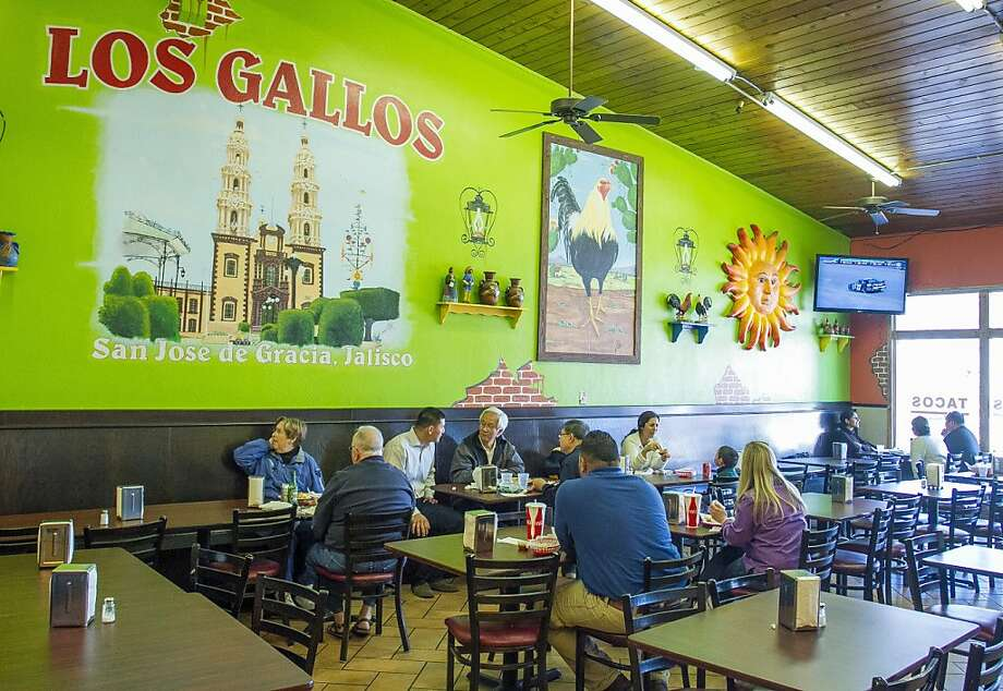 Los Gallos Taqueria in Redwood City features a large dining room, above, with specialties including the chili relleno plate, left, and the wet chicken super burrito, below. Photo: John Storey, Special To The Chronicle