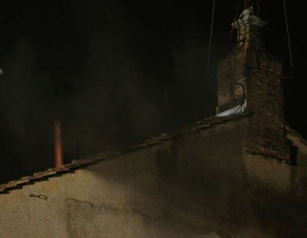 Black smoke emerges from the chimney on the roof of the Sistine Chapel, in St. Peter's Square at the Vatican, Tuesday, March 12, 2013. The black smoke indicates that the new pope has not been elected yet. Photo: Dmitry Lovetsky