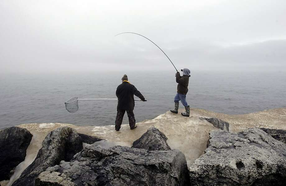 Spears fishing: Adam Wilson stands ready with the net as fellow fishermen Jason Spears reels in a steelhead from Lake Michigan along the rocks at Pere Marquette Park in Muskegon, Mich. Photo: Ken Stevens, Associated Press