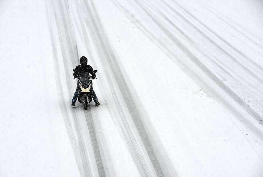 Bet he wishes he took the car instead: A scooter rider slowly negotiates the treacherous N118 highway around Paris during a heavy snowstorm. Photo: Franck Fife, AFP/Getty Images