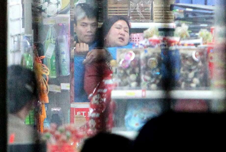 Standoff in the aisles:A man holds a saleswoman at knife point inside a store in Zhengzhou, China's Henan province. The man's relatives finally persuaded him to set the woman free. Photo: Afp, AFP/Getty Images
