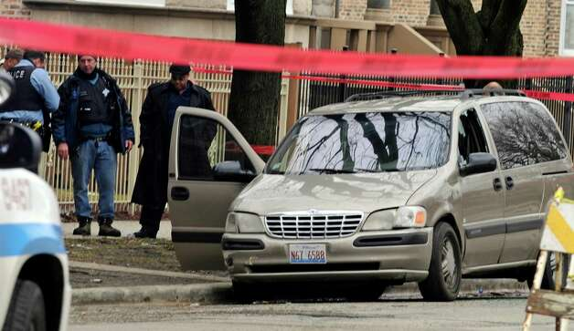 In this Monday, March 11, 2013 photo, Chicago Police investigate at the scene of a shooting where 6-month-old Jonylah Watkins, was shot five times whie her father was changing her diaper in a parked minivan in Chicago's Woodlawn neighborhood. The van can be seen with the window shattered from the shooting. The Cook County Medical Examiner's office announced Tuesday morning that the baby died from her wounds. Her father, Jonathan Watkins, remains in critical condition at Northwestern Memorial Hospital.   CHICAGO LOCALS OUT, MAGS OUT Photo: Chicago Sun-Times, John H. White