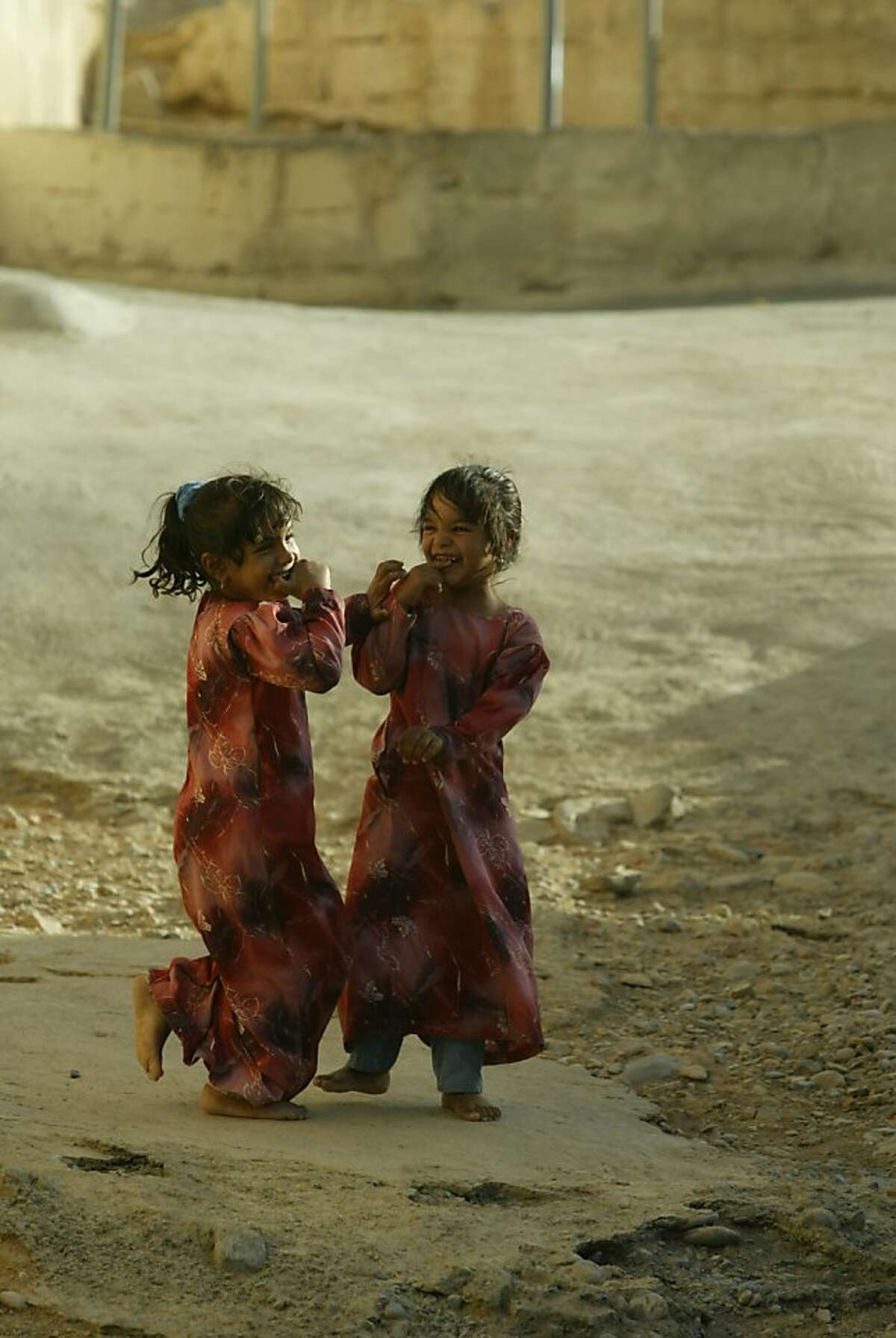 TRAVEL OMAN -- Sisters in colorful clothes practice being adorable for the camera in the ancient mud-brick city of Al Hamra. Spud Hilton / The Chronicle