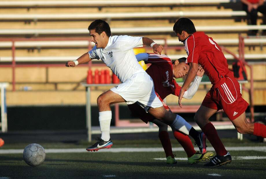 Westside senior midfielder Joseph Baez, from left, beats Bellaire defenders Samuel Calderon and Lazaro Moreira during their game at Butler Stadium. Freelance photo by Jerry Baker Photo: Jerry Baker, Freelance