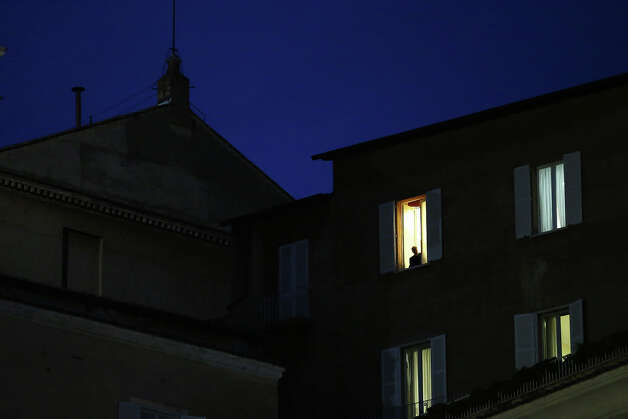 A man looks out of a window next to the chimney on the roof of the Sistine Chapel as people await news of whether the College of Cardinals have elected a new Pope on March 12, 2013 in Vatican City, Vatican. Pope Benedict XVI's successor is being chosen by the College of Cardinals in Conclave in the Sistine Chapel. The 115 cardinal-electors, meeting in strict secrecy, will need to reach a two-thirds-plus-one vote majority to elect the 266th Pontiff. Photo: Peter Macdiarmid, Getty Images / 2013 Getty Images