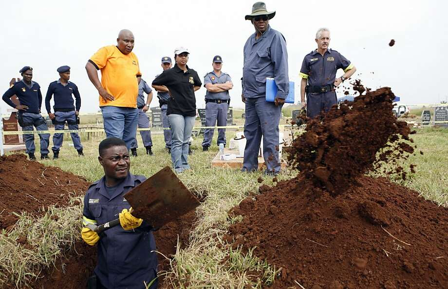 A South African police forensic officer in Johannesburg digs up the grave of one of the two young activists last seen alive 24 years ago at the home of Nelson Mandela's ex-wife. Photo: Themba Hadebe, Associated Press
